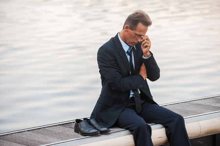 Feeling lonely and depressed. Depressed mature businessman touching his face with hand while sitting barefoot at the quayside  photo