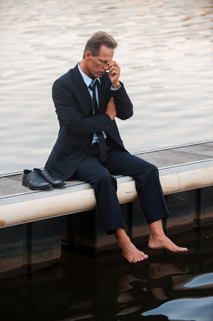 depressed man: Failed again. Depressed mature businessman touching his face with hand while sitting barefoot at the quayside