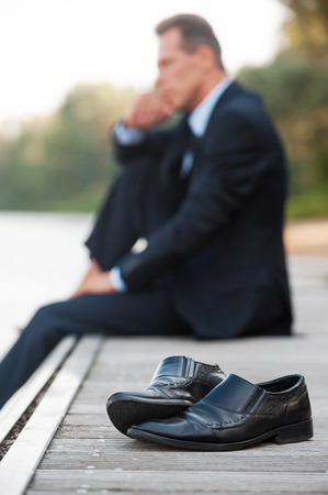 He needs to stay alone now. Side view of thoughtful businessman holding hand on chin and looking away while sitting barefoot at the quayside and with shoes laying on foreground photo