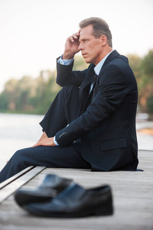 Worried about his business. Side view of thoughtful businessman holding hand on chin and looking away while sitting barefoot at the quayside and with shoes laying on foreground photo