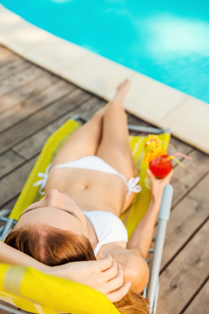 Total relaxation by the pool. Top view of beautiful young woman in white bikini holding cocktail in her hand while relaxing in deck chair near the pool photo