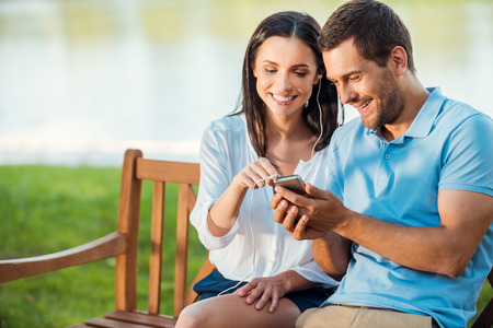 mobile phone: Enjoying favorite their music together. Beautiful young loving couple sitting on the bench together while woman pointing mobile phone and smiling