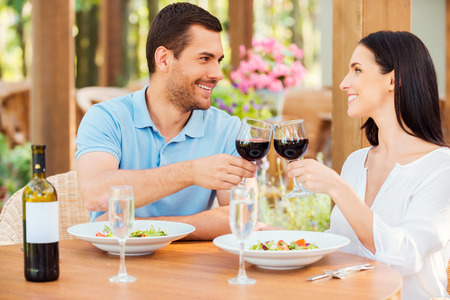 Cheers! Beautiful young loving couple toasting with red wine and smiling while relaxing in outdoors restaurant together photo