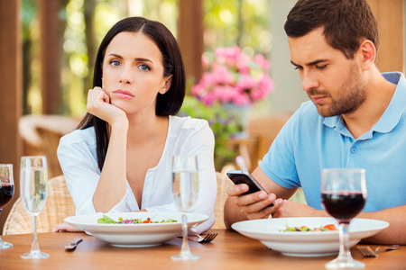 This is the worst date ever. Depressed young woman holding hand on chin and looking at camera while her boyfriend talking on the mobile phone at outdoors restaurant