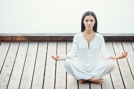 lotus position: Yoga is my life. Beautiful young woman in white clothing meditating on seaside