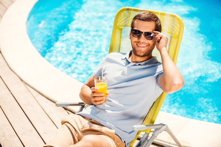This is the life! Top view of cheerful young man in polo shirt sitting at the deck chair and holding glass with orange juice photo
