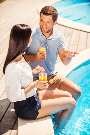 Spending time poolside together. Top view of happy couple in casual wear sitting poolside and talking  photo
