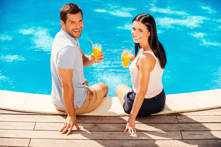 Enjoying their summer vacation. Top view of happy couple in casual wear holding glasses with orange juice and smiling while sitting poolside together  photo