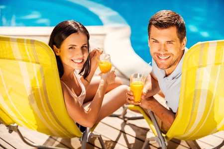 Spending carefree time poolside. Happy couple holding cocktails and smiling while sitting at the deck chairs by the pool photo
