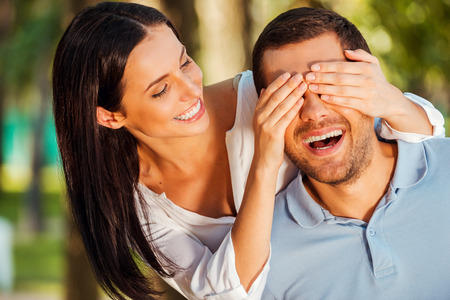 Guess who? Beautiful young woman covering eyes of her boyfriend and smiling while both standing outdoors photo