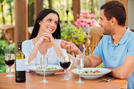Enjoying every minute being close to him. Beautiful young loving couple talking and smiling while relaxing in outdoors restaurant together  photo