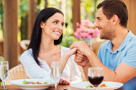 te amo: Te amo! Hermosa joven pareja de enamorados cogidos de la mano y mirando el uno al otro mientras se relaja en el restaurante al aire libre junto Foto de archivo