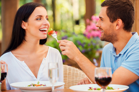 Try my meal! Handsome young man feeding his girlfriend with salad and smiling while both relaxing in outdoors restaurant  photo
