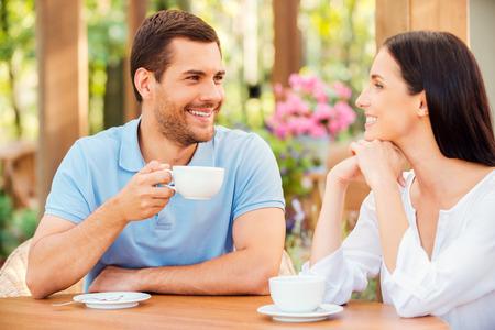 Ze houden van tijd met elkaar doorbrengen. Mooie jonge verliefde paar drinken koffie in openlucht koffie samen