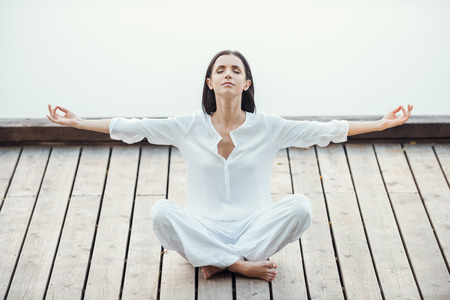 all in one: Finding peace and balance. Beautiful young woman in white clothing sitting in lotus position and keeping eyes closed while meditating outdoors Stock Photo