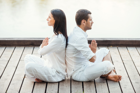 away from it all: In peace with universe. Side view of beautiful young couple in white clothing meditating outdoors together while sitting back to back in lotus position