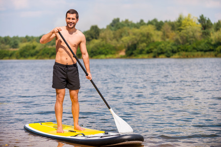paddleboard: Great day to paddle. Handsome young man surfing on his paddleboard and smiling Stock Photo