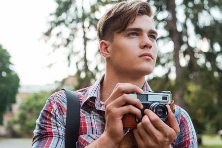 one teenager: Just inspired. Handsome young man holding digital camera and looking away while standing outdoors Stock Photo