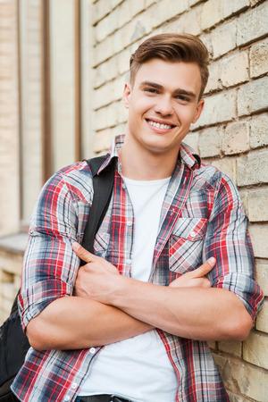 大学での時間を楽しんでください。片方の肩にバックパックを運ぶとレンガの壁にもたれながら笑顔のハンサムな若者