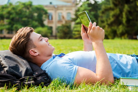 Finding a peaceful place to relax. Side view of handsome young man working on digital tablet while lying on grass  photo