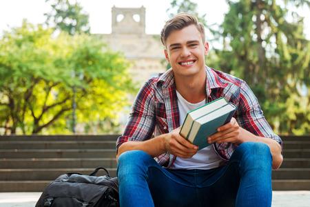 handsome men: Topo di biblioteca Felice. Handsome studente maschio in possesso di libri di testo e sorridente mentre seduto al scalinata all'aperto con edificio universitario in background