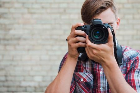 카메라에 미소 지어 라! 벽돌 벽에 서있는 동안 자신의 디지털 카메라로 초점을 확신 확신 젊은 남자