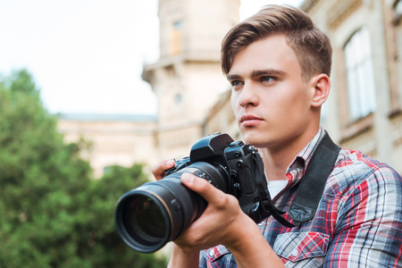 one teenager: Ready to shoot. Handsome young man holding digital camera and looking away while standing outdoors
