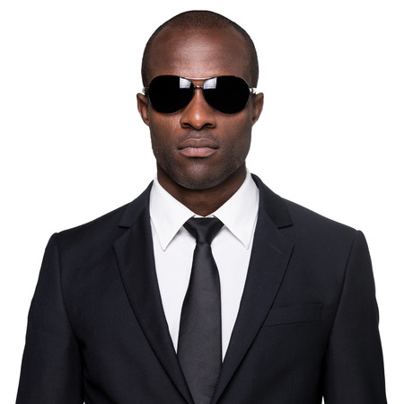 bodyguard: Elegant and cool. Serious young African man in formalwear and sunglasses looking at camera while standing isolated on white background