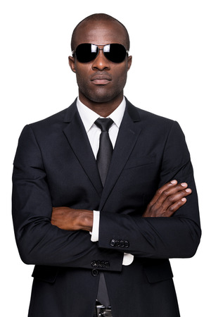Cool and handsome. Serious young African man in formalwear and sunglasses keeping arms crossed and looking at camera while standing isolated on white background