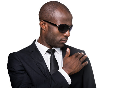 adjusting: Looking just perfect. Portrait of serious young African man in formalwear and sunglasses adjusting his jacket while standing isolated on white background