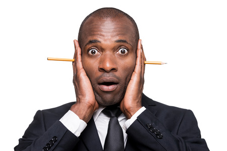 Something wrong... Surprised young African man in formalwear holding head in hands with pencil sticking out of it while standing isolated on white background photo