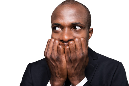 Terrified businessman. Terrified young African man in formalwear holding fingers in mouth and looking away while standing isolated on white background photo