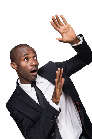 Please no! Terrified young African man in formalwear looking up and gesturing while standing isolated on white background photo