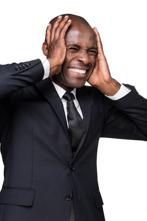 Stressed businessman. Depressed young African man in formalwear holding head in hands and grimacing while standing isolated on white background photo