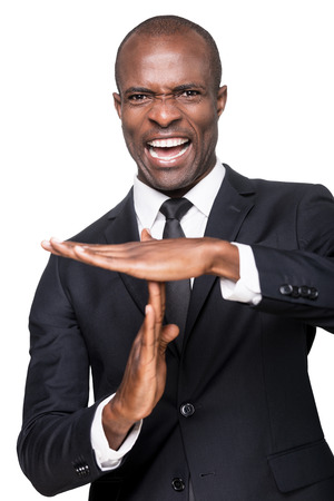 time out: Time out! Furious young African man in formalwear gesturing time out while standing isolated on white background Stock Photo