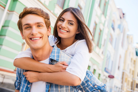 Having fun together. Low angle view of beautiful young loving couple standing outdoors together while woman hugging her boyfriend and smiling Foto de archivo