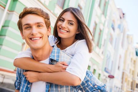 Plezier samen. Lage hoek bekijken van mooie jonge liefdevol paar staande samen buitenshuis, terwijl vrouw knuffelen haar vriendje en glimlachen