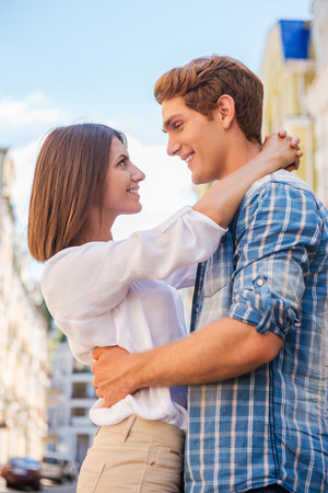 Loving couple. Low angle view of beautiful young loving couple hugging and looking at each other while standing outdoors Stok Fotoğraf
