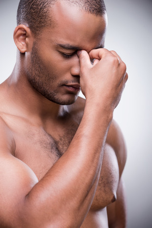 Portrait of shirtless African man touching his nose and keeping eyes closed while standing against grey background photo
