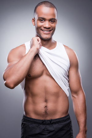 standing against: Handsome young African man taking off his tank top and smiling while standing against grey background Stock Photo