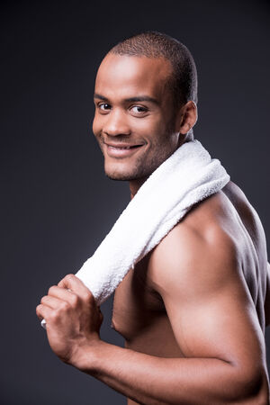 looking over shoulder: Young shirtless African man carrying towel on shoulders and looking over shoulder with smile while standing against grey background