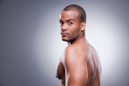 over black: Young shirtless African man looking over shoulder while standing against grey background Stock Photo