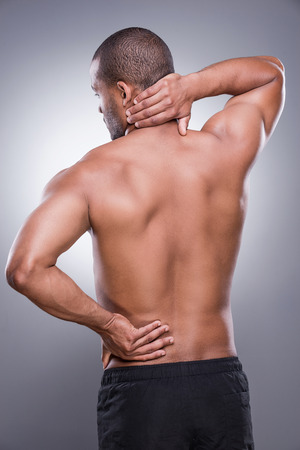 muscle injury: Rear view of young muscular African man touching his hip and neck while standing against grey background