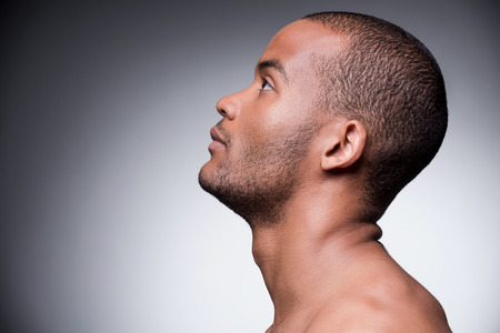 face side: Side view of young shirtless African man looking up while standing against grey background