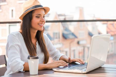 internet cafe: Tomando ventajas de conexi�n Wi-Fi. Joven y bella mujer en el sombrero cobarde trabajando en la computadora port�til y sonriendo mientras sentado al aire libre Foto de archivo