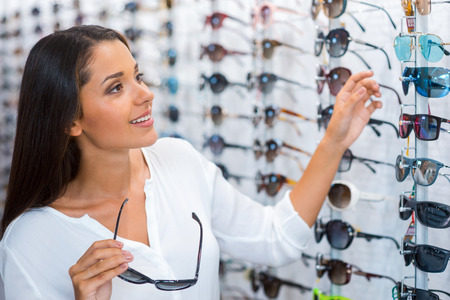 eyesight: Choosing the right sunglasses. Beautiful young woman choosing sunglasses in store