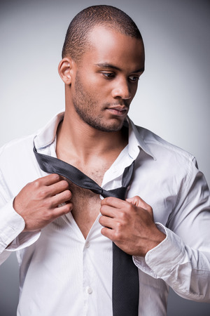 Taking off his necktie. Confident young black man taking off his necktie while standing against grey background photo