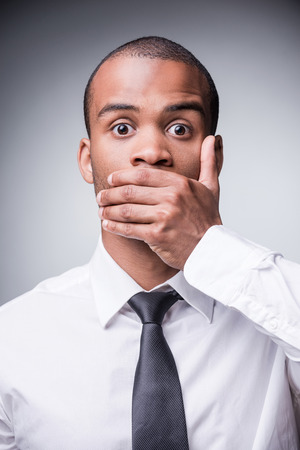 Saying no evil. Shocked young African man in shirt and tie covering mouth with hand while standing against grey background photo