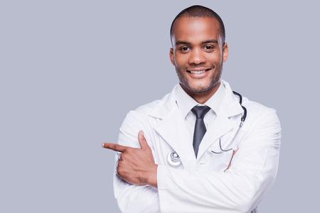 자신감 남성 의사. 회색 배경에 서있는 동안 명랑 아프리카 의사가 멀리 가리키는 웃 고