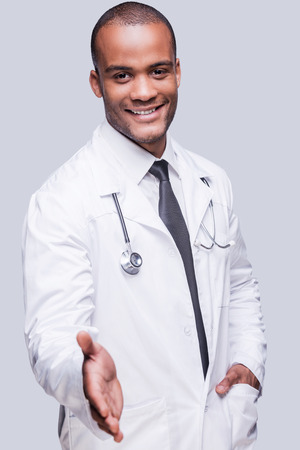 shaking out: Always ready to help you. Cheerful African doctor stretching out hand for shaking while standing against grey background
